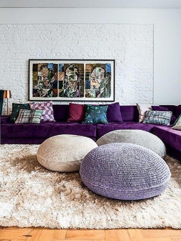 O sofá de canto roxo acomoda várias pessoas no ambiente
