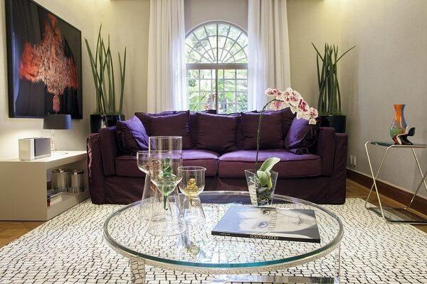 O sofá roxo contrasta com as cores claras das paredes e tapete da sala de estar