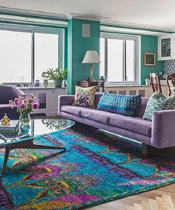 O sofá roxo de 3 lugares conversa diretamente com o tapete estampado