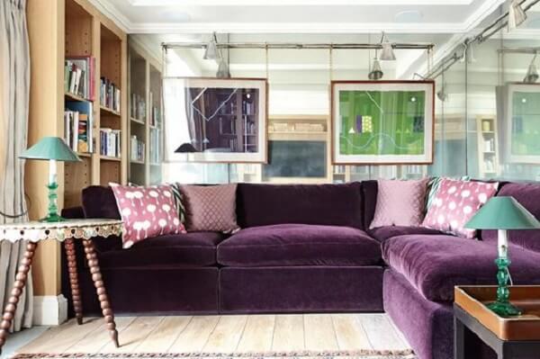 O sofá roxo de canto delimita a área da sala