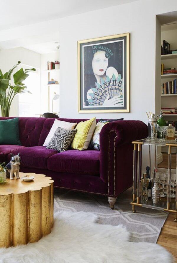 O sofá roxo escuro quebra a neutralidade da decoração desse ambiente