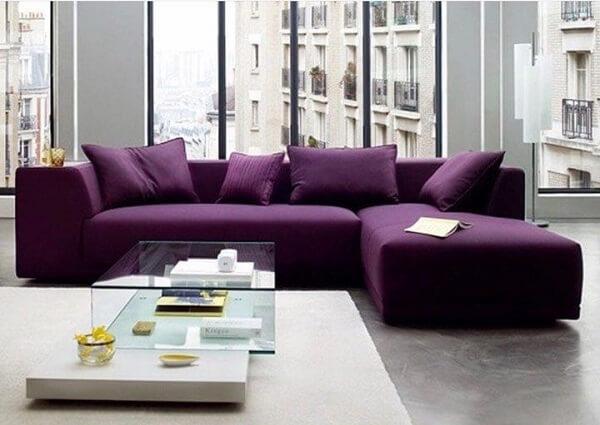 O sofá roxo escuro se destaca na decoração do ambiente