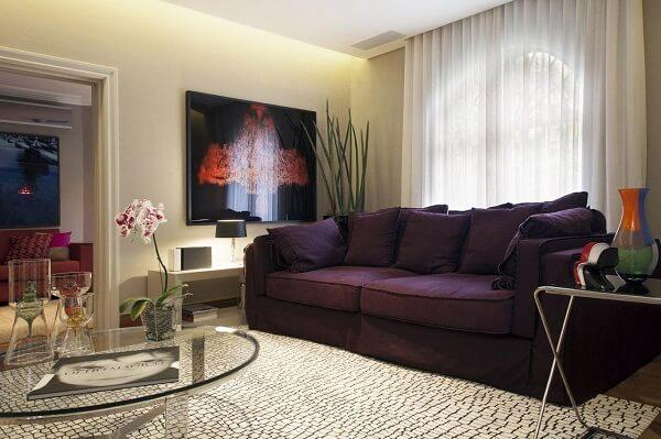 O sofá roxo traz um toque de cor para a decoração da sala de estar