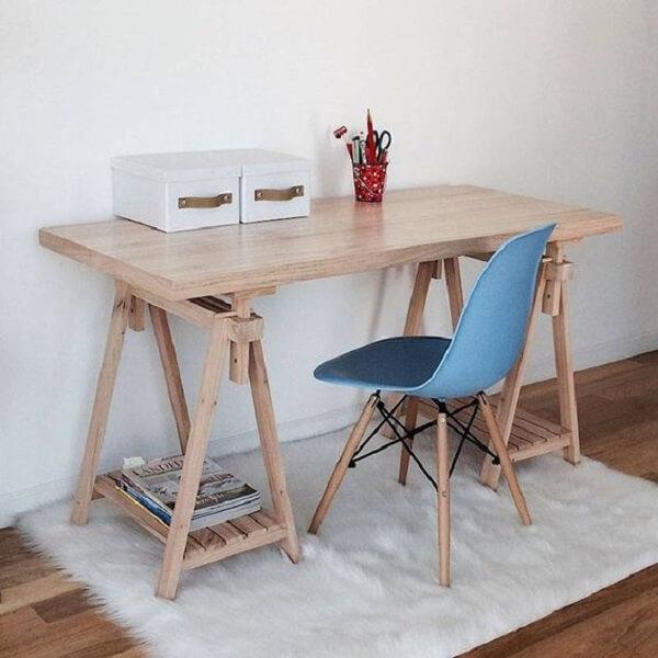 O tapete branco peludo traz conforto aos pés de quem senta na escrivaninha de madeira