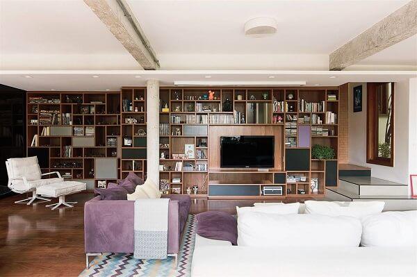 O tapete com estampa geométrica apresenta nuances em roxo conversando diretamente com o sofá roxo do local