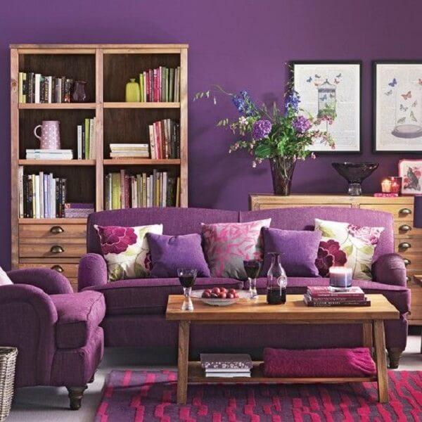 Os móveis em madeira trazem um contraste para a poltrona e sofá roxo