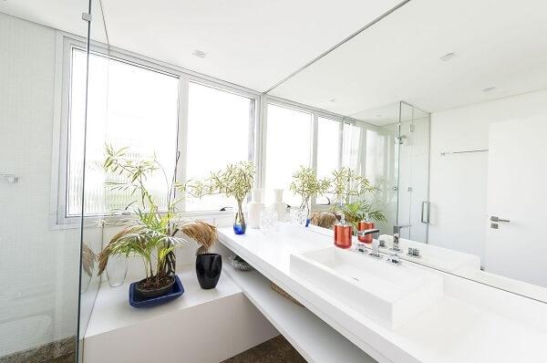 Os móveis em marcenaria branca se misturam com a cuba de apoio para banheiro