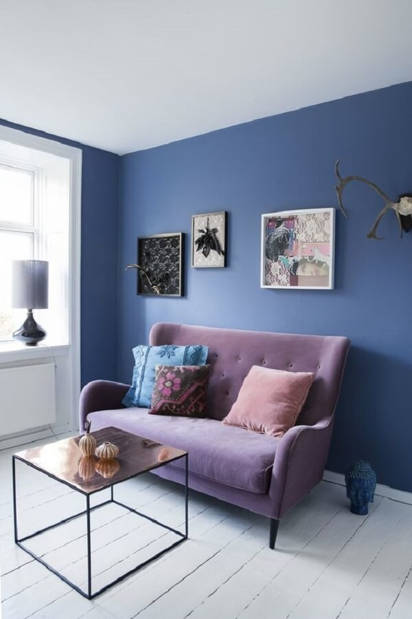 Parede azul e sofá roxo formam uma combinação ousada