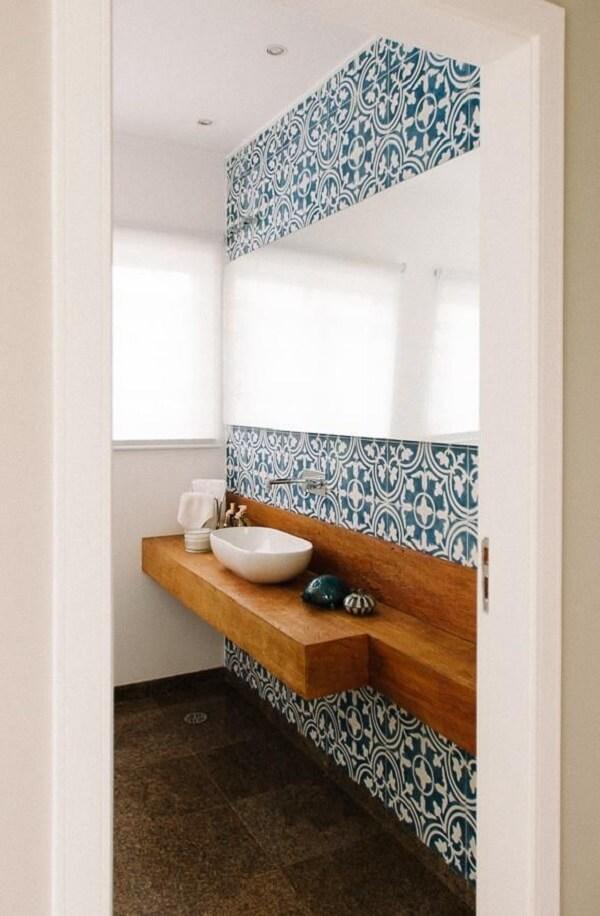 Parede com ladrilho azul e bancada de madeira com cuba de apoio para banheiro formam uma combinação harmoniosa