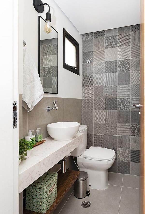 Parede com ladrilho hidráulico cinza e cuba de apoio para banheiro decoram o espaço