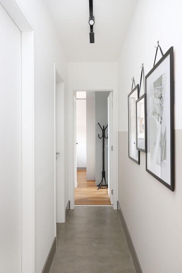 Piso de cimento queimado e iluminação com luminária para corredor pequeno do tipo trilho