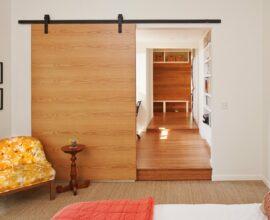 Porta de correr de madeira para quarto com trilho aparente