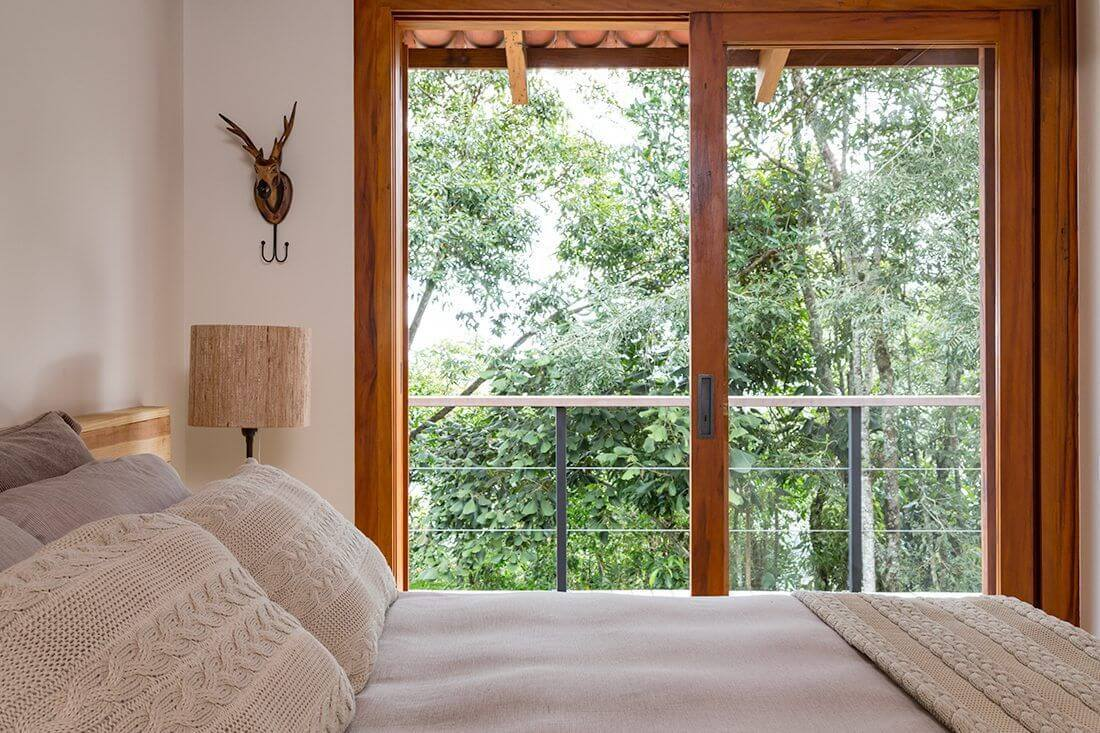 A porta de correr para quarto de vidro com acabamento em madeira permite a visão da paisagem do entorno do imóvel