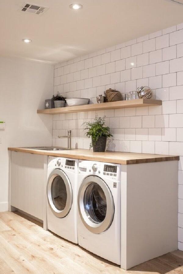 Revestimento branco para lavanderia e piso de madeira decoram o ambiente
