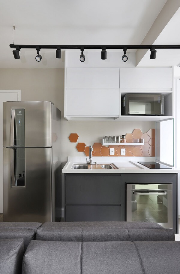 Revestimento de parede laranja em formato sextavado decora a cozinha