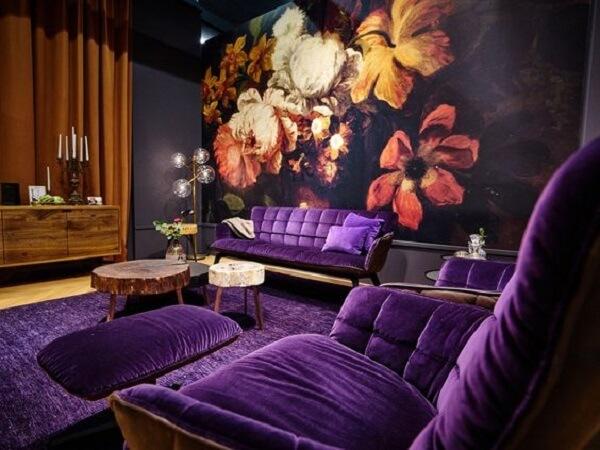 Sofá roxo e papel de parede floral decoram esse ambiente