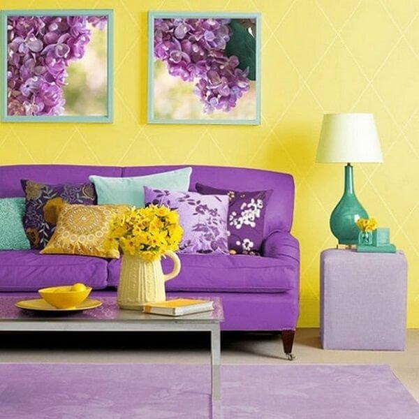 Sala com sofá roxo e objetos decorativos amarelo e verde