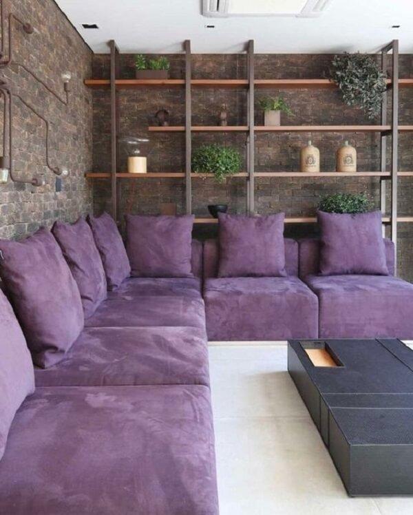 Sala contemporânea com sofá de canto roxo e parede de tijolinho aparente