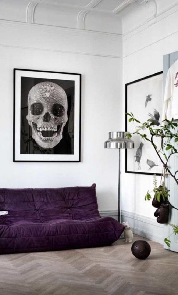 Sofá roxo com pegada de futton se destaca na decoração da sala