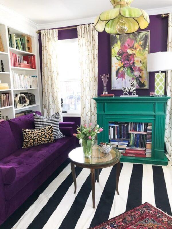 Sofá roxo escuro com tapete listrado decoram o espaço