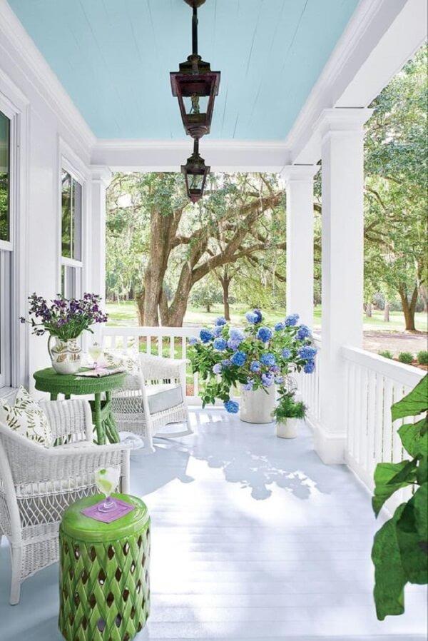 Terraço com decoração suave em tons de azul, branco e verde contam com a presença da charmosa arandela colonial