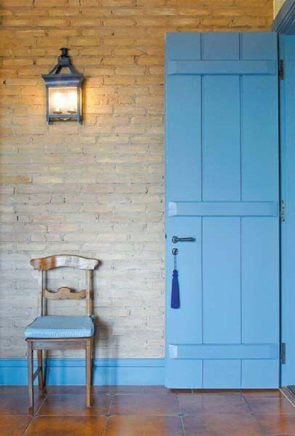Tijolinho aparente, porta de madeira e arandela colonial formam uma linda combinação