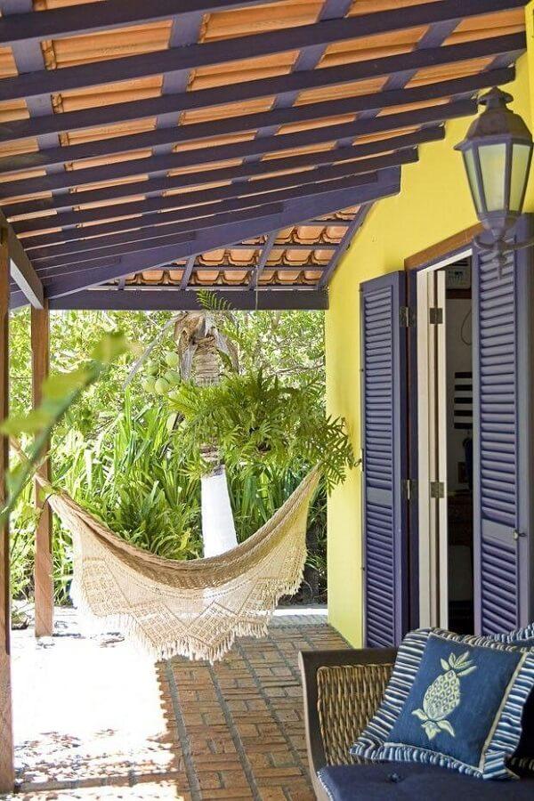 Varanda colorida com estrutura aparente e arandela colonial preta
