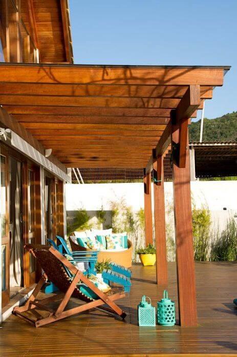 Varanda de casa de praia com pergolado de madeira