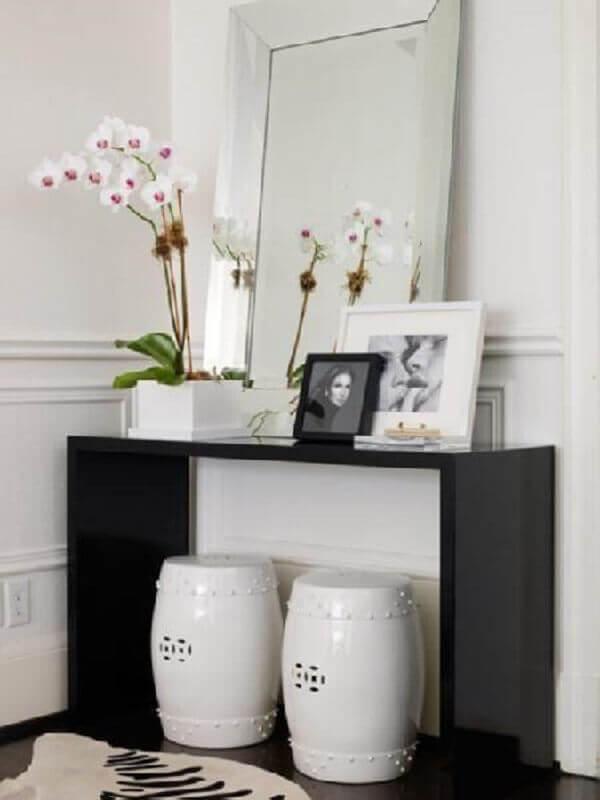 aparador pequeno preto decorado com quadros e vasos de planta Foto Pinterest