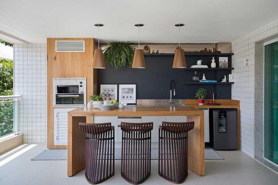 banquetas altas para área gourmet moderna com churrasqueira planejada em varanda Foto As Arquitetas