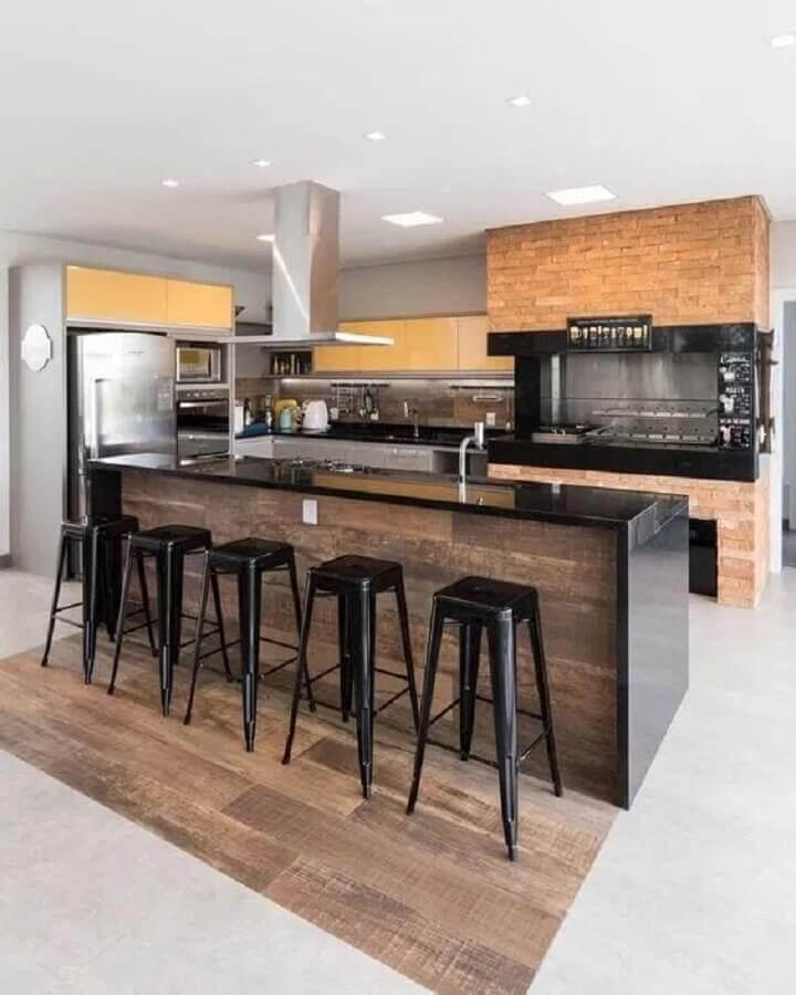 banquetas modernas para área gourmet decorada com bancada preta e churrasqueira grande Foto Histórias de Casa