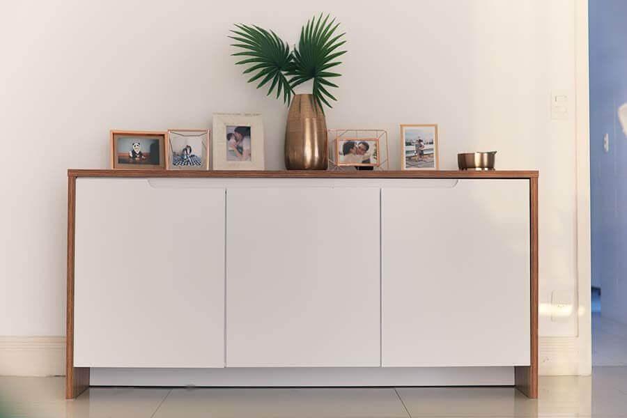 buffet pequeno branco decorado com quadros e vaso de planta Foto Just Lia