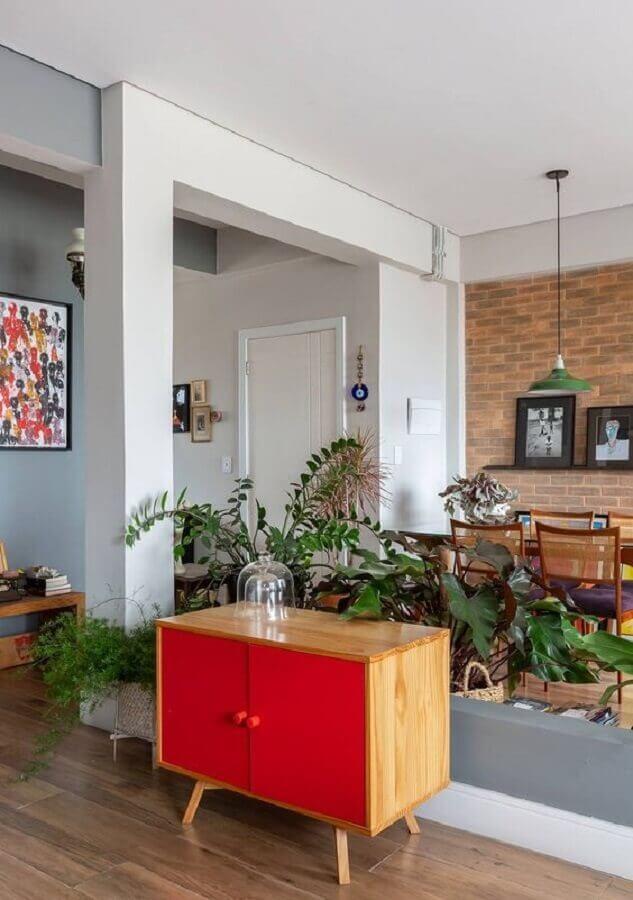 buffet pequeno para sala de jantar decorada com vasos de plantas e parede de tijolinho Foto Histórias de Casa