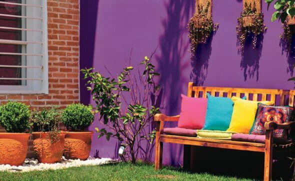 Jardim com parede roxa e móveis coloridos