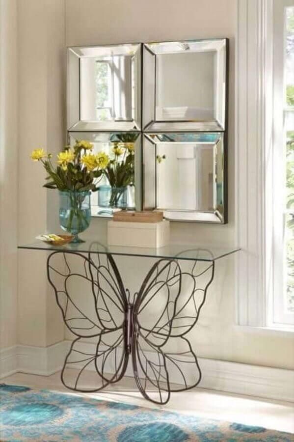 corredor decorado com aparador pequeno  de vidro com base em formato de borboleta Foto Pinterest