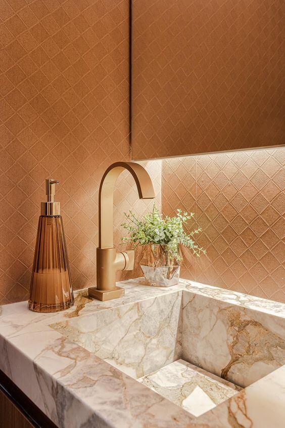 Banheiro luxuoso com cuba de mármore e detalhes em dourado