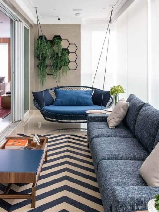 decoração de varanda de apartamento com balanço suspenso e sofá azul Foto Pinterest