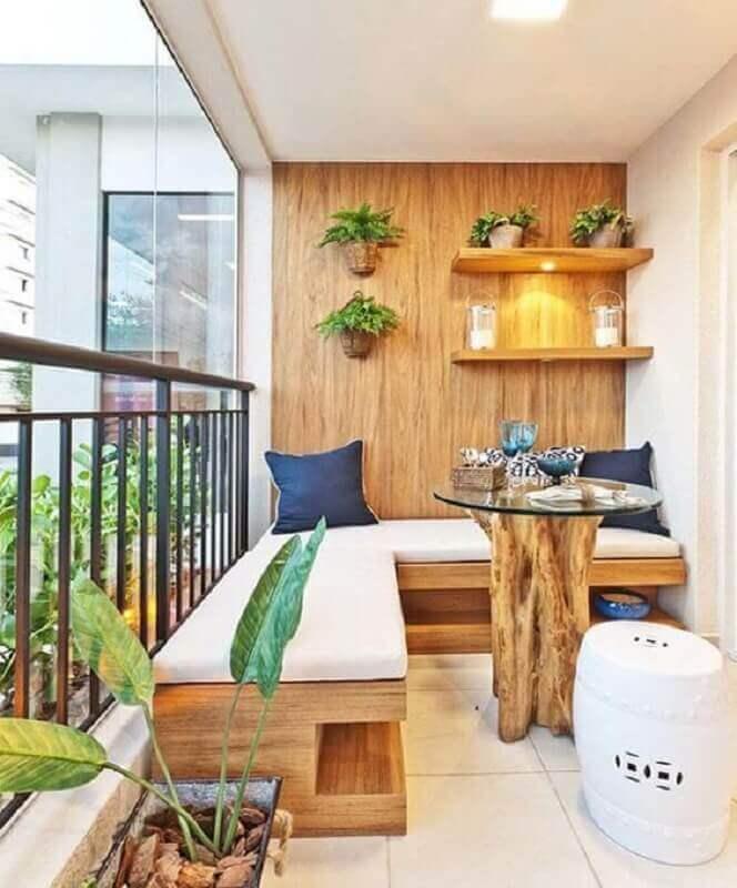 decoração de varanda de apartamento com sofá de canto de madeira e mesa de vidro com base de madeira Foto Pinterest