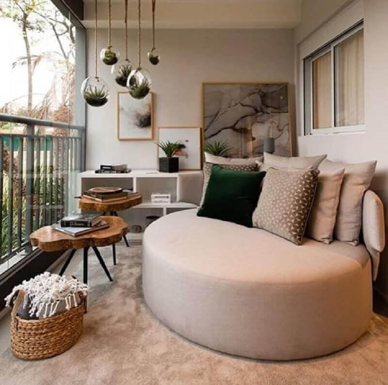 decoração de varanda de apartamento com sofá redondo e mesa lateral de madeira rústica Foto LVA Home