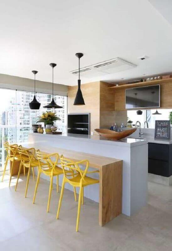 decoração de varanda de apartamento gourmet com banquetas amarelas para bancada de madeira  Foto Karen Pisacane