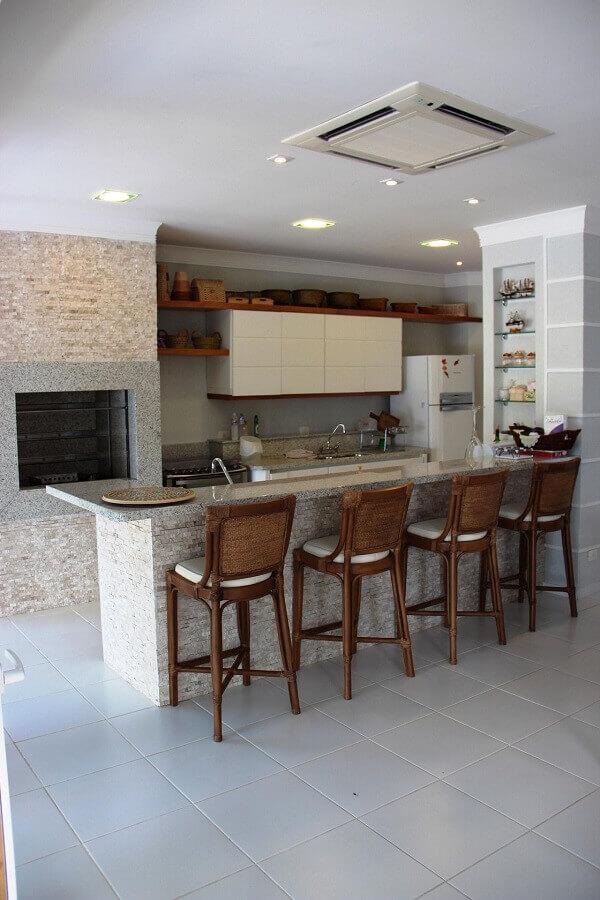 decoração simples com banquetas de madeira para área gourmet com churrasqueira Foto Bender Arquitetura