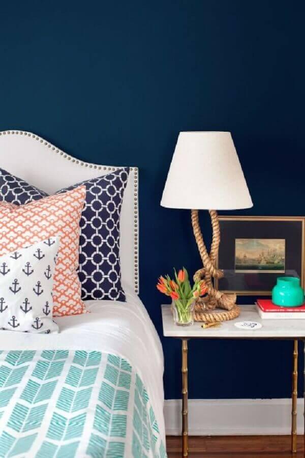 mesa de canto para quarto de casal decorado com parede azul marinho  Foto Better Homes and Gardens