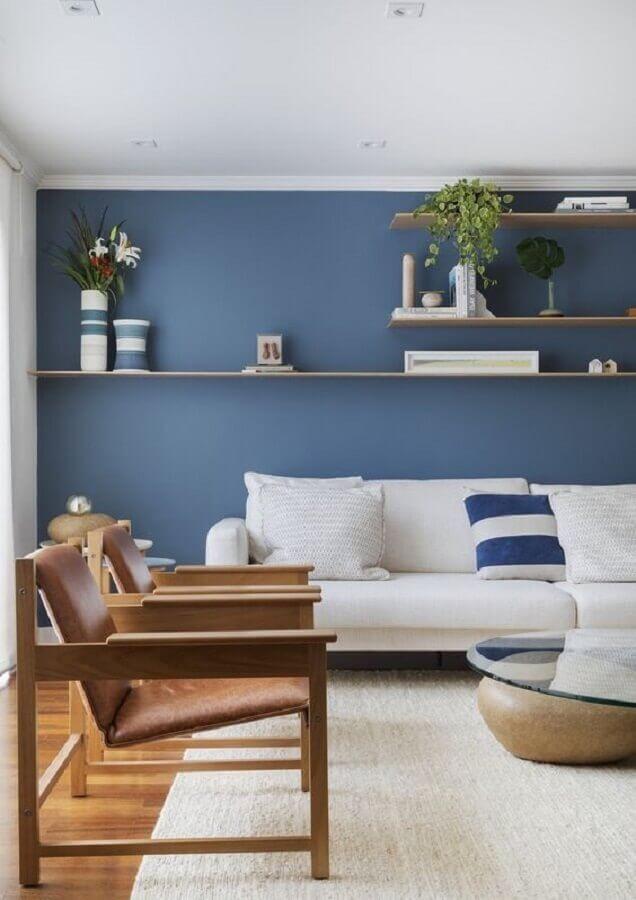 parede na cor azul para decoração de sala com sofá branco e poltronas de madeira  Foto VOA Arquitetura