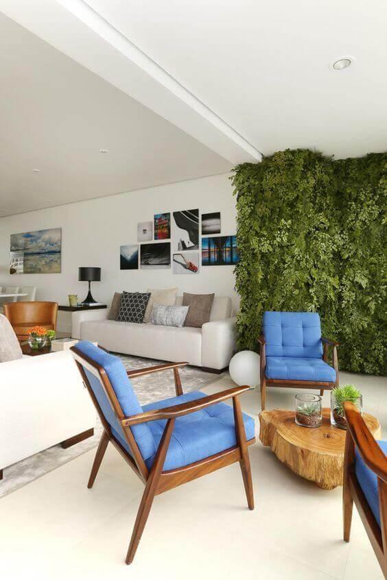 Poltrona capitonê na sala com jardim vertical