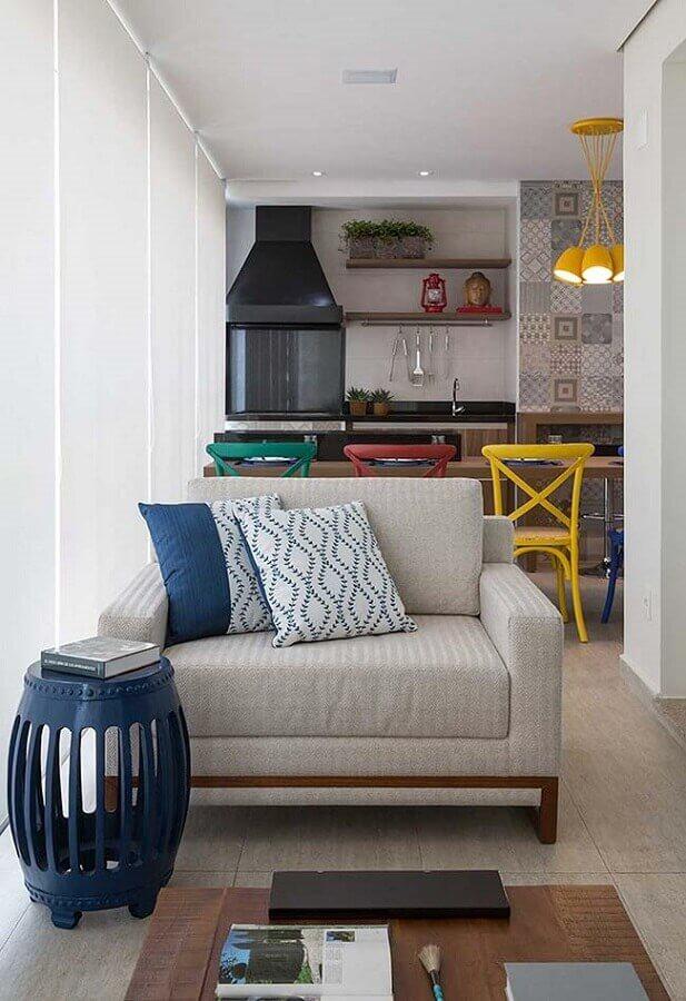 poltrona cinza para varanda de apartamento decorada com banquetas coloridas e churrasqueira de vidro  Foto Histórias de Casa