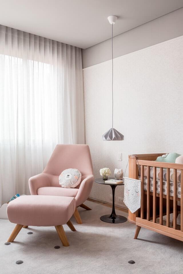 Quarto de bebê com poltrona rosa e puff