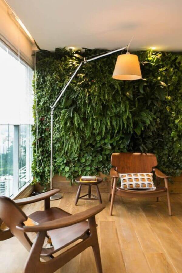 poltrona de madeira para varanda de apartamento decorada com jardim vertical e luminária de piso Foto Decostore