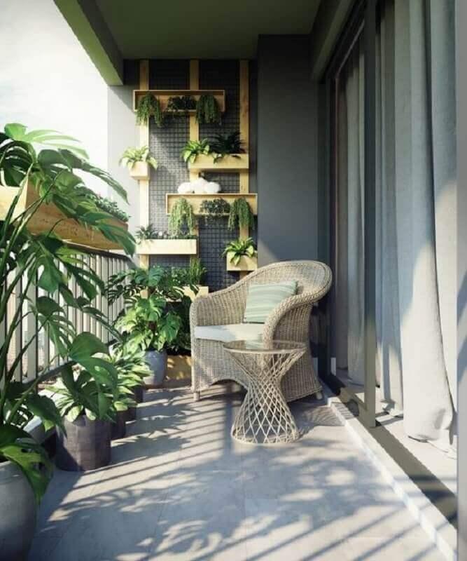 poltrona de vime para varanda cinza decorada com vários vasos de plantas Foto Home Designing