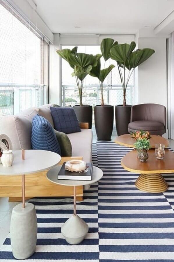 poltronas para varanda de apartamento decorado com tapete listrado e vasos grandes de planta  Foto GP Life Decor