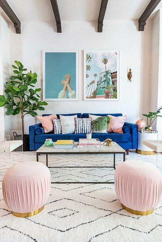 Sala com sofá azul e móveis em rosa claro